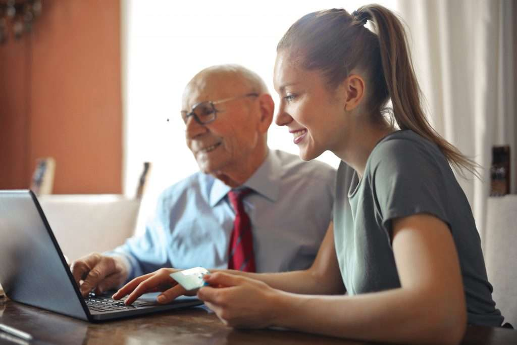 Image of a daily money manager helping out a senior citzen with a credit card bill.