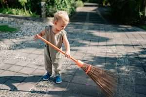 Teaching children value of money: a child sweeping.